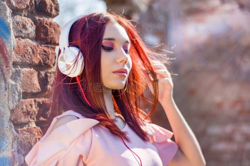 Lyssnande musik för ursnygg rödhårig mandam i hörlurar på suddiga utomhus- bakgrunds- och väggtegelstenar royaltyfri fotografi
