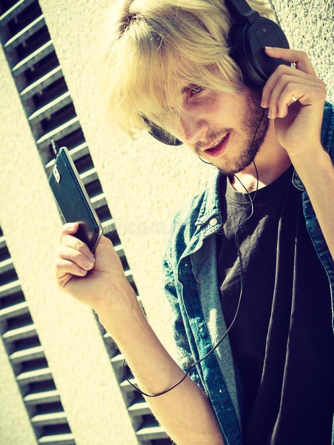 Lyssnande musik f?r Hipsterman till och med h?rlurar royaltyfria foton