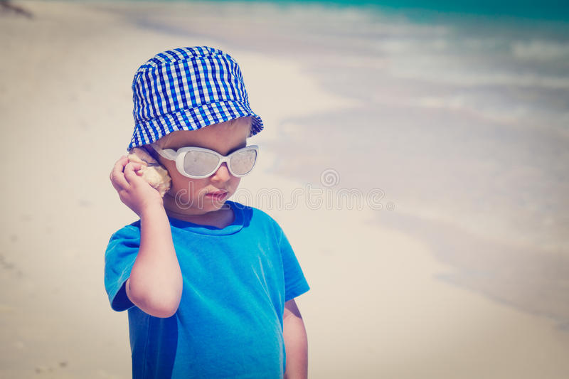 Lyssnande snäckskal för pys på stranden arkivfoton