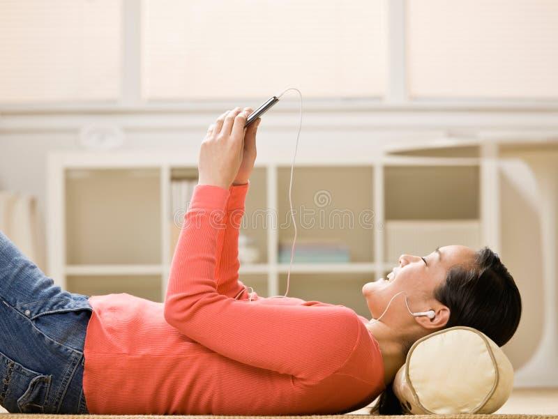 lyssnande spelare för musik mp3 till kvinnan arkivbilder