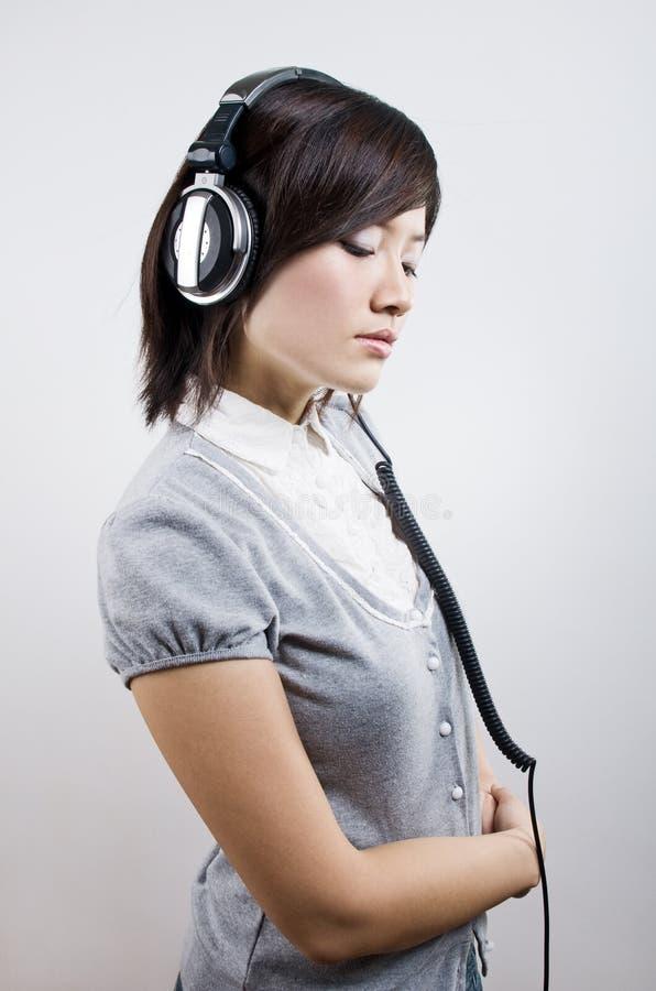 lyssnande unga musikkvinnor royaltyfria bilder