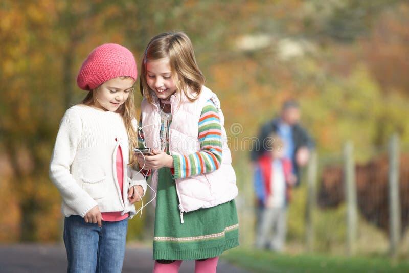 lyssnande utomhus spelare mp3 för flicka till två barn royaltyfri bild