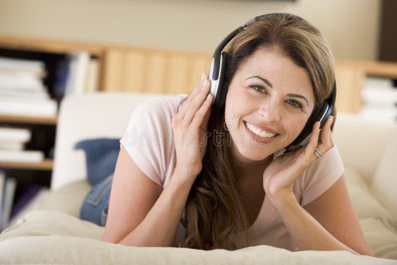 lyssnande vardagsrum för hörlurar till kvinnan royaltyfria bilder