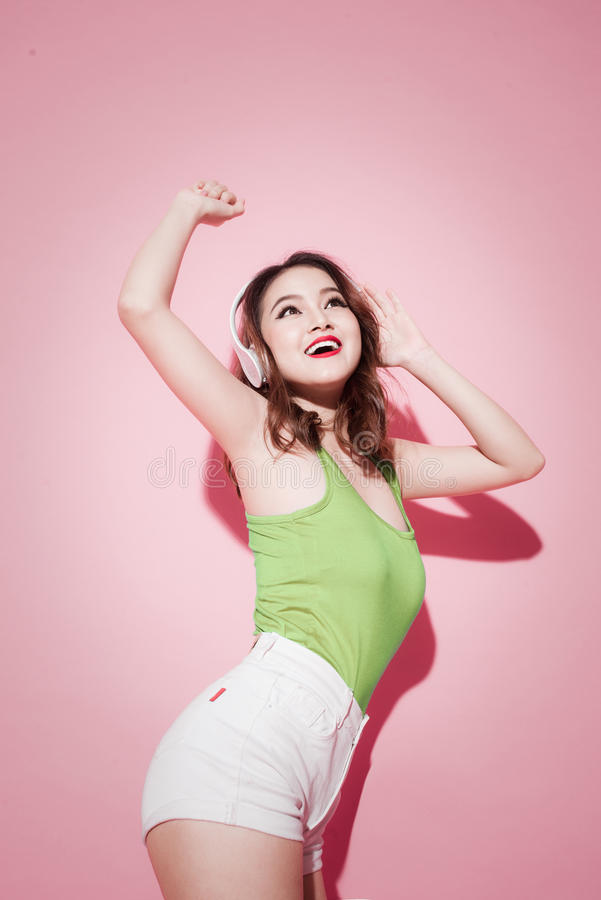 Lyssnar den nätta asiatiska flickan för livsstilen som har gyckel, musik på rosa färger med royaltyfria bilder