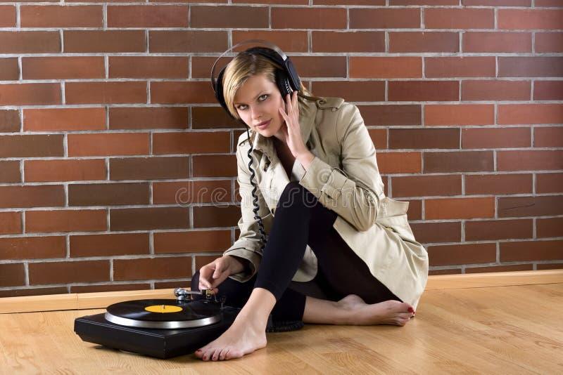 lyssnar musiktrenchcoatkvinnor royaltyfri foto