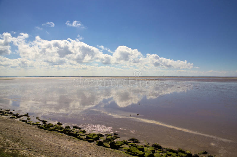 Lytham St Annes beach. Blue sky and cloudscape reflected in the sea off Lythan St Annes beach in Lancashire, England royalty free stock photo