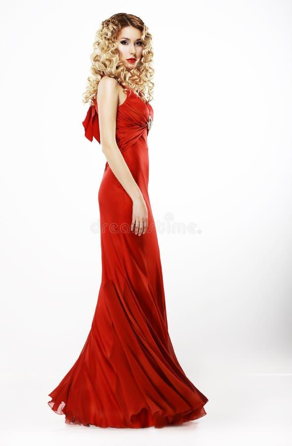 Lyx. Full längd av den eleganta damen i röd satängliknande klänning. Burrigt blont hår royaltyfri fotografi