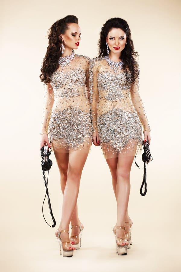 Lyx. Två moderiktiga kvinnor som går i skinande ljusa klänningar arkivfoto