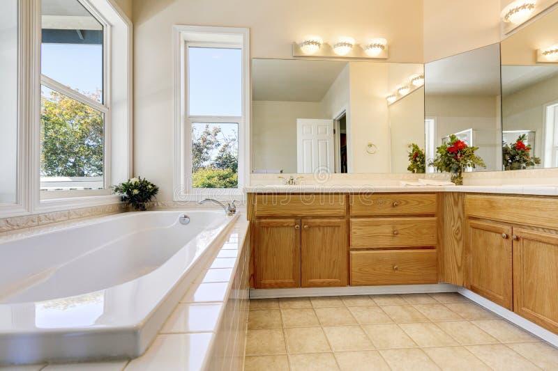 Lyxig badruminre med träkabinetter och det vita badkaret royaltyfri foto