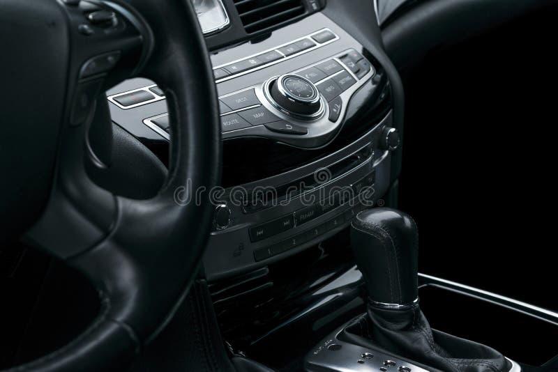 Lyxig bil inom Inre av den moderna bilen för prestige automatisk kugghjulförskjutning Svart perforerad lädercockpit Massmediakont arkivfoto