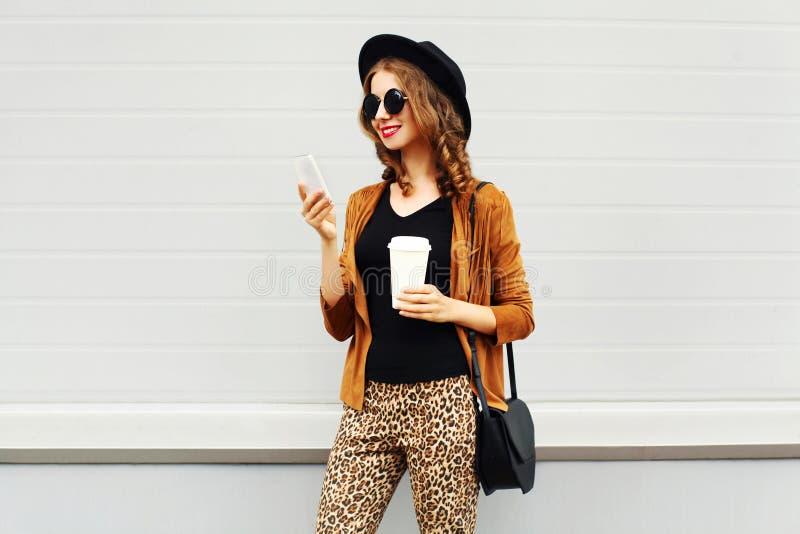 Lyxig blick för höst, nätt kall le ung kvinna med kaffekoppen genom att använda smartphonen som går i staden, lycklig kvinnlig mo royaltyfria bilder
