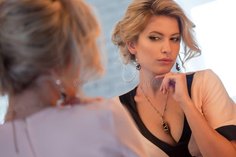 Lyxig blond kvinna för skönhet Det attraktiva barnet modellerar i den härliga klänningen som framme sitter av spegeln, till primp arkivbilder
