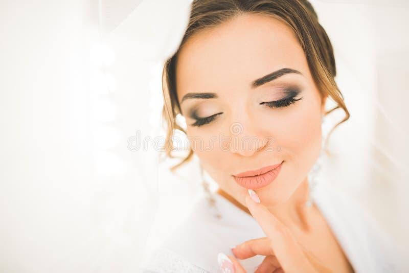 Lyxig brud i den vita klänningen som poserar, medan förbereda sig för bröllopceremonin fotografering för bildbyråer