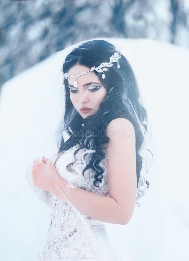 Lyxig brunett i en vit klänning arkivfoton