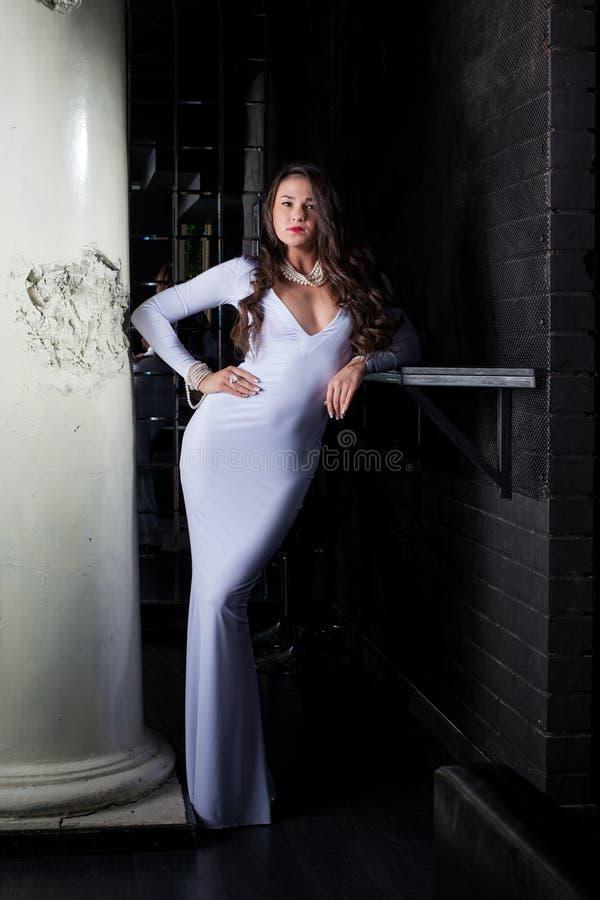 Lyxig brunett som poserar i elegant vitklänning fotografering för bildbyråer
