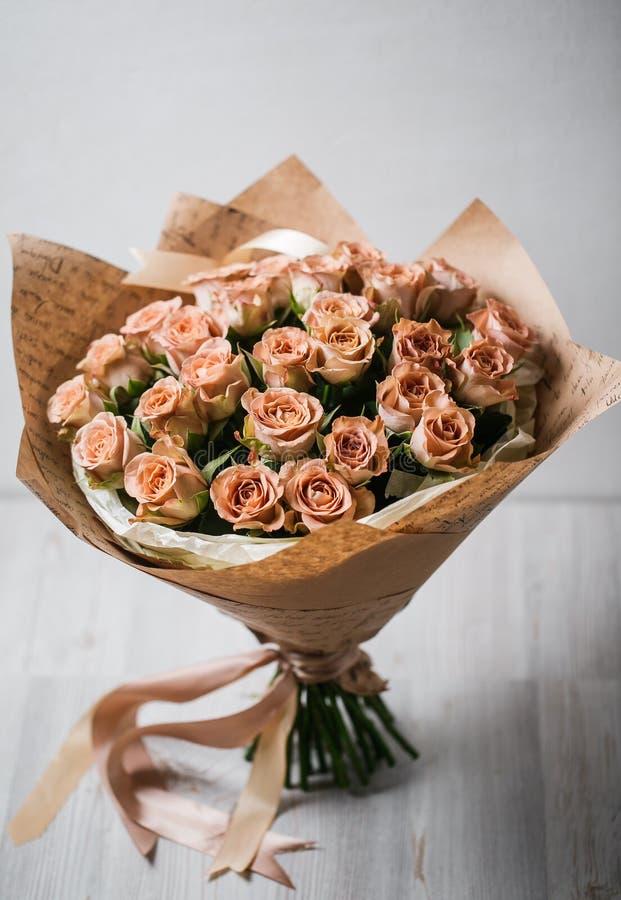 Lyxig bukett av mycket små rosor som lägger på trätabellen i kafé mellan kaffecappuccino och exponeringsglasvinrankan, film som f royaltyfria bilder