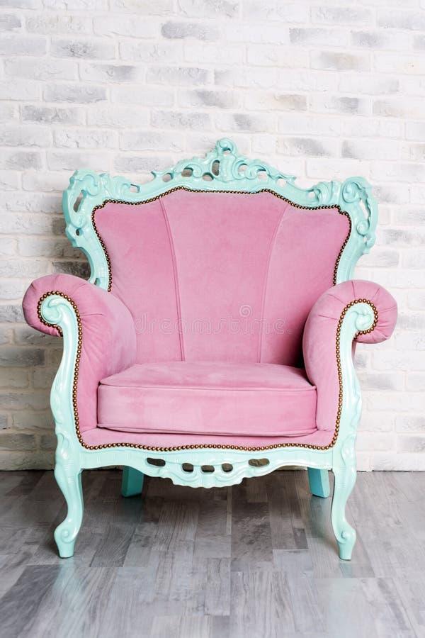 Lyxig fåtölj för rosa tappning på vit bakgrund för tegelstenvägg elegantt möblemang royaltyfri bild