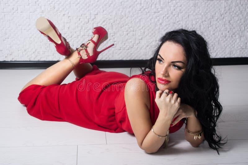 Lyxig flicka i en röd klänning royaltyfri foto