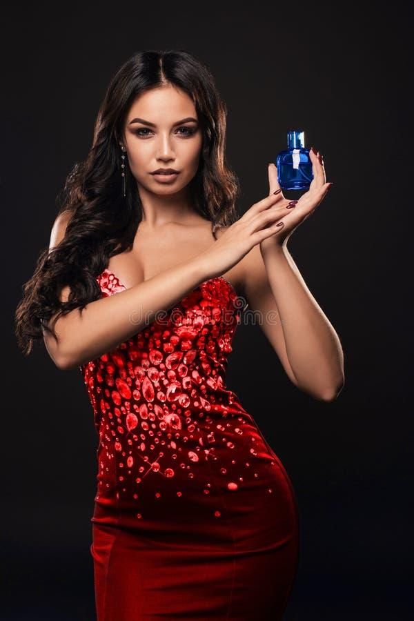 Lyxig flicka med en flaska av doft i händerna på en mörk bakgrund royaltyfria bilder