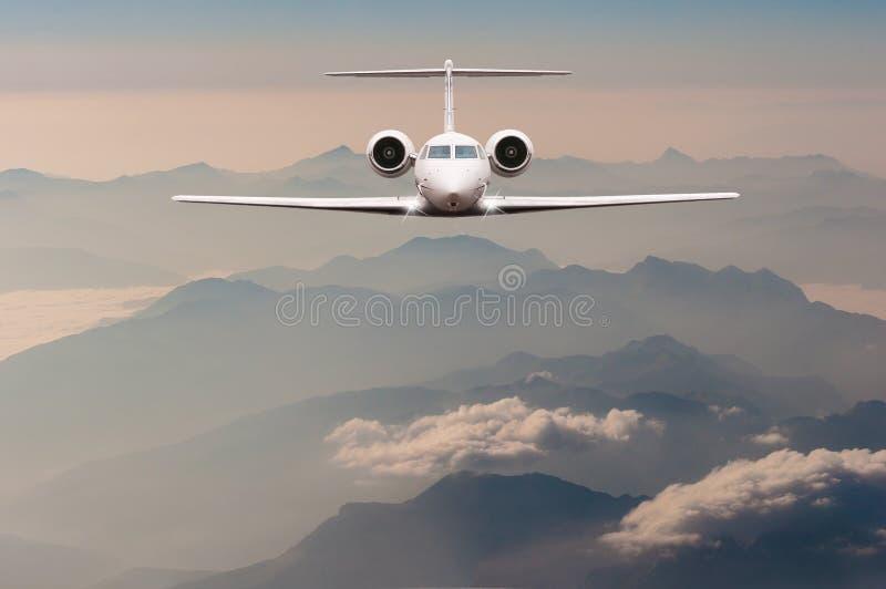 Lyxig flygplanfluga över moln och fjällängberget på solnedgång Främre sikt av ett stort passagerare- eller lastflygplan, affär royaltyfria foton