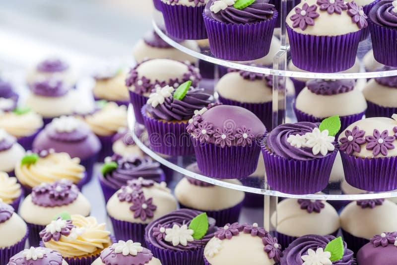 Lyxig gifta sig muffin med purpurfärgade blommor och bevekelsegrunder royaltyfri fotografi