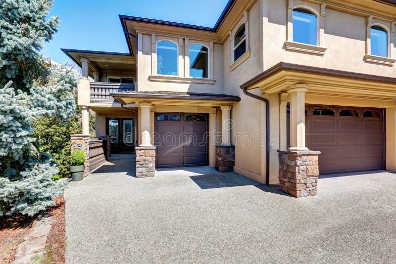 Lyxig husyttersida med kolonner och brunt parkera bilen i garage dörrar arkivfoto
