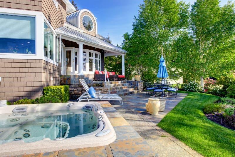 Lyxig husyttersida med mäktig trädgårddesign, uteplatsområde och varma badar arkivbild