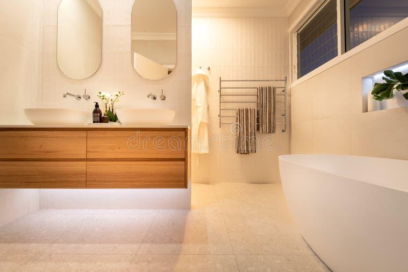 Lyxig inhemsk badrumdusch och fåfänga med ekskänkenheter, badet, den vita färgintrigen och ljus belysning arkivfoton