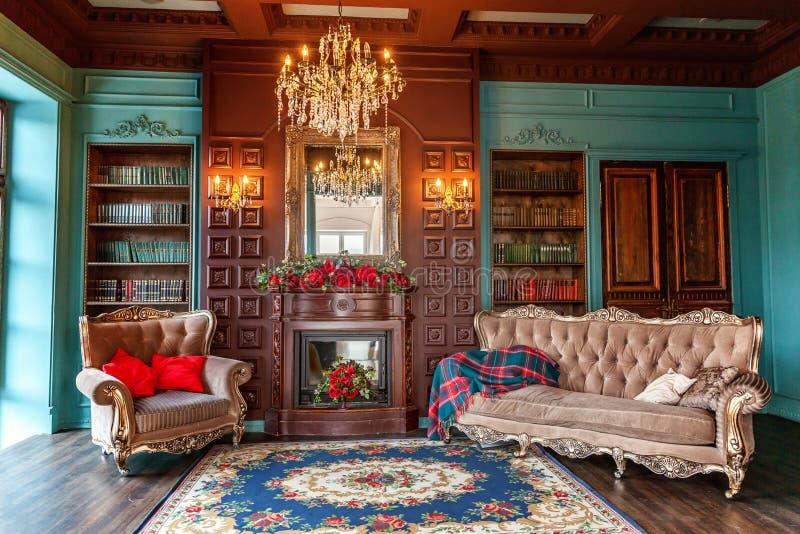 Lyxig klassisk inre av det hem- arkivet Vardagsrum med bokhyllan, böcker, armstol, soffan och spisen Rengöring och modernt royaltyfria bilder