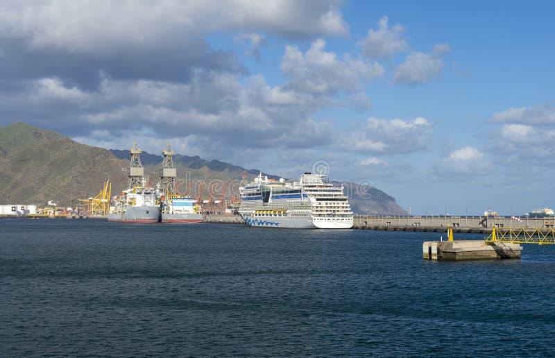 Lyxig kryssare i hamn med berg i bakgrund arkivbild