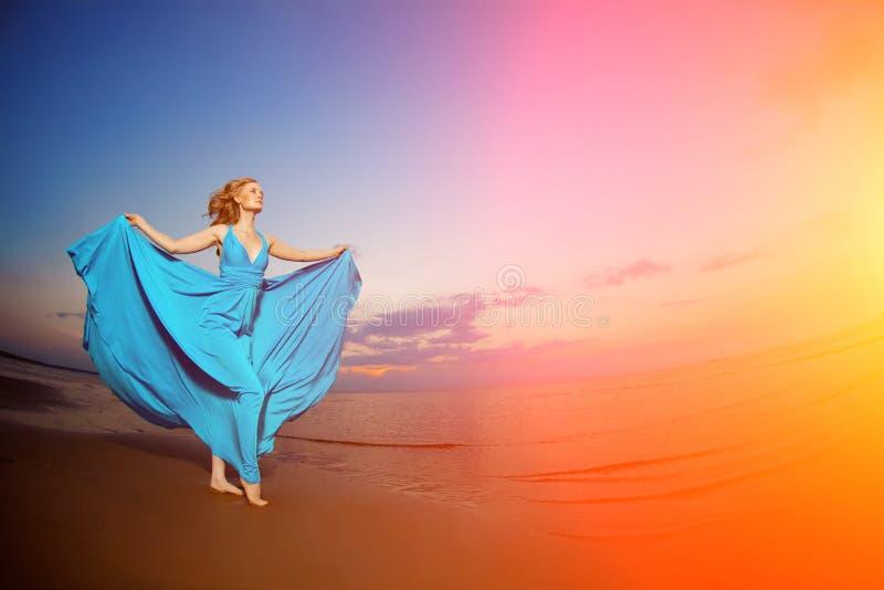 Lyxig kvinna i en lång blå aftonklänning på stranden _ fotografering för bildbyråer