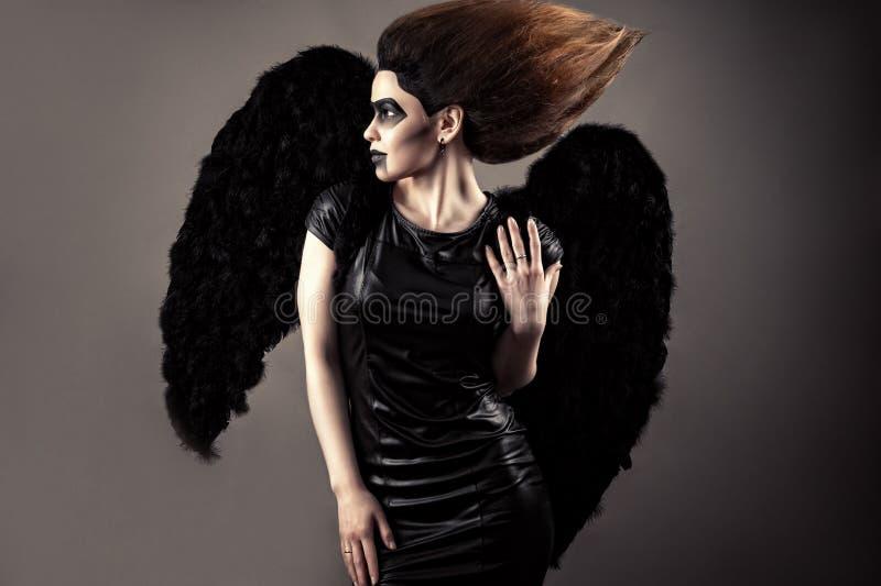 Lyxig kvinna med frodig hår- och mörkermakeup med svarta vingar royaltyfri bild