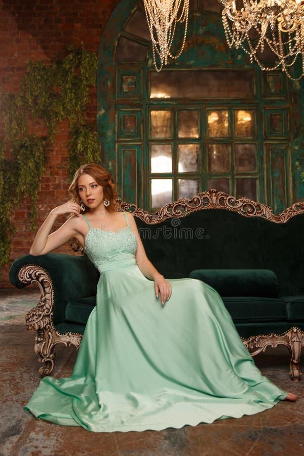 Lyxig kvinnamodell i enfärgad klänning som sitter på en tappningsoffa Skönhetflicka med en bedöva makeup och frisyr fotografering för bildbyråer