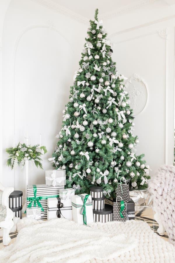 Lyxig lägenhet som dekoreras för jul Xmas-träd med gåvor under i vardagsrum arkivbilder