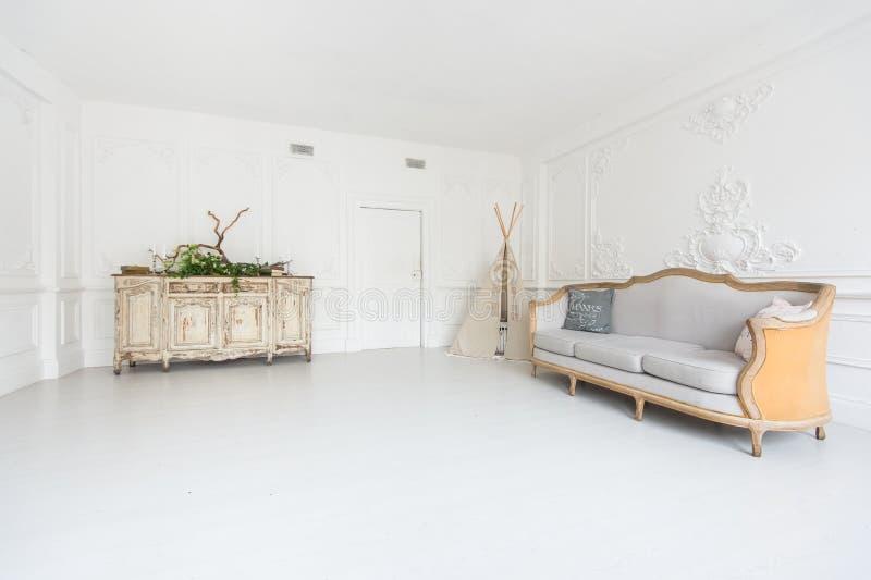 Lyxig ljus inre av rummet med stuckaturen på väggarna, soffan, vigvammet och byrån som dekoreras med växter arkivfoton