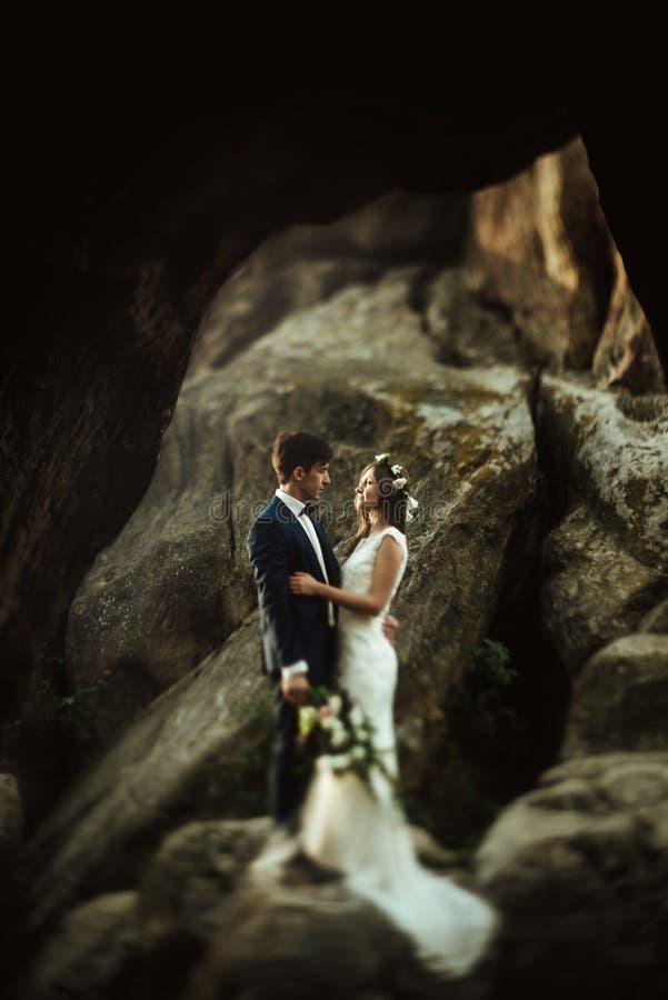 Lyxig lycklig brud och stilfullt brudgumanseende på stenar, ovanlig sikt fotografering för bildbyråer