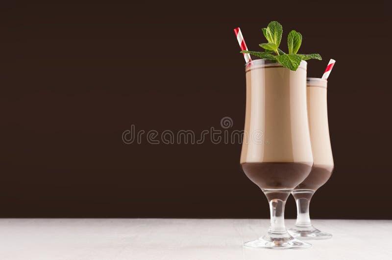 Lyxig milkshake för söt choklad i vinglas med den nya gröna mintkaramellen och rött randigt sugrör på mörk brun bakgrund,  royaltyfri foto