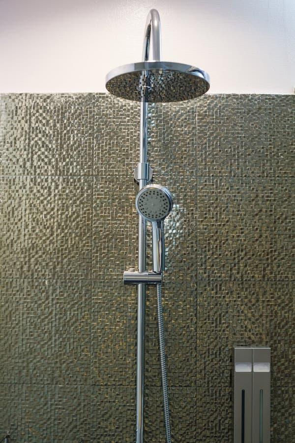 Lyxig modern dusch för rostfritt ståltakregn, vattenkran för duschhuvud och hållare i badrum på guld- dekorera tegelplattaväggbac arkivbilder