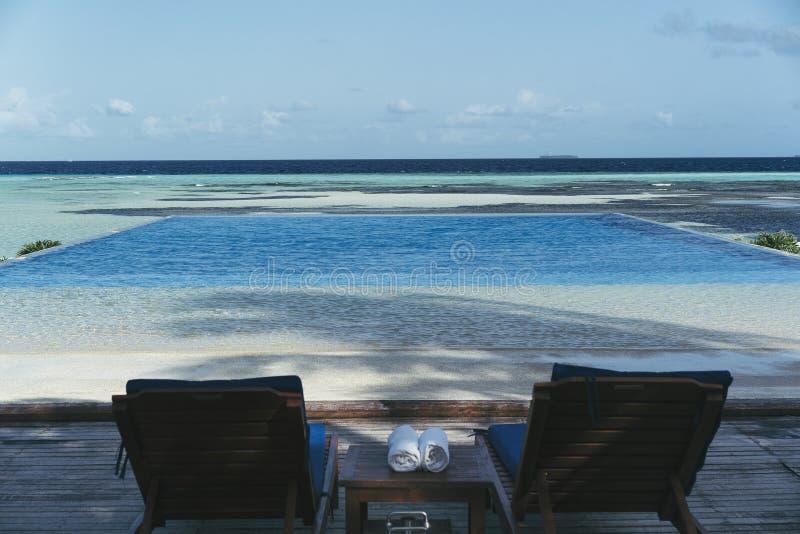 Lyxig oändlighetspöl med två stolar, handdukar och det genomskinliga havet royaltyfri bild