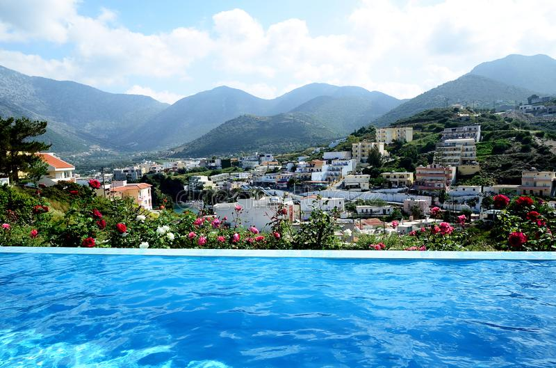 Lyxig oändlighetssimbassäng på en privat villa med härlig havs- och bergsikt royaltyfri bild