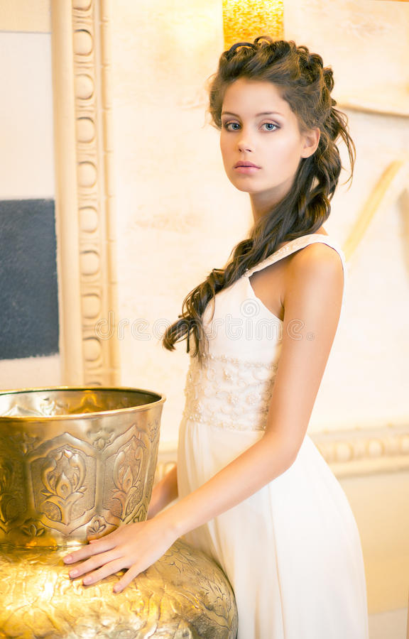 Lyxig Posh brunett i vitklänning. Orientalisk antik guld- dekor royaltyfri foto