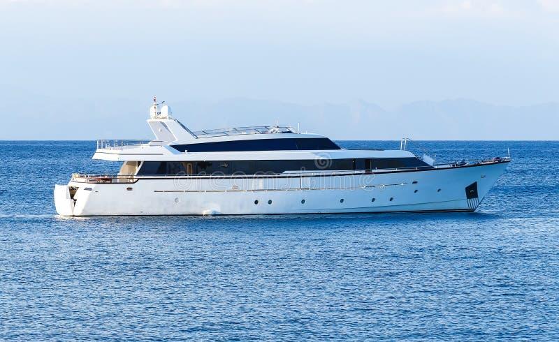 Lyxig privat motorisk yacht under väg på det tropiska havet med pilbågevågen royaltyfri bild