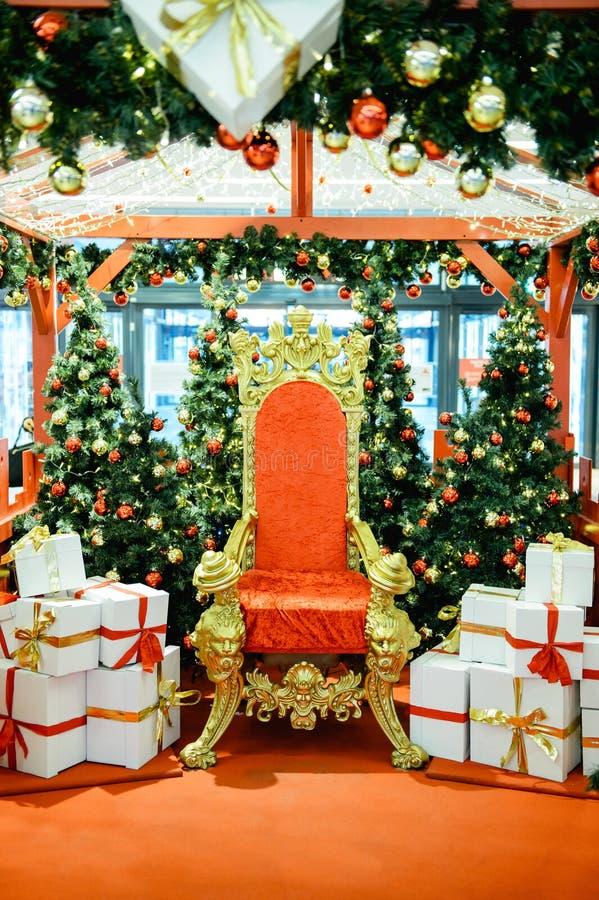 Lyxig röd stolSanta Claus biskopsstol och gåvor royaltyfri foto