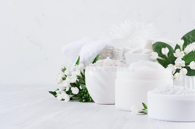 Lyxig ren vit skönhetsmedeluppsättning av naturprodukter för kräm- kropp- och hudomsorg -, salta, skura och små blommor på vitt t royaltyfri bild