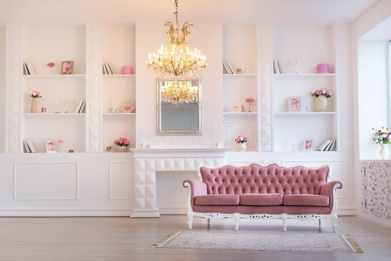 Lyxig rik vardagsruminredesign med eleganta klassiska möblemang- och vägggarneringar Stort ljust vitt rum med arkivbilder