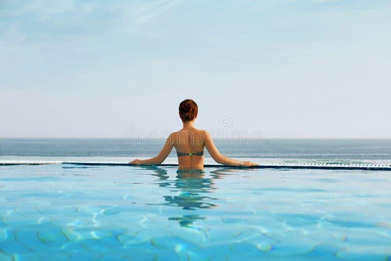 Lyxig semesterloppkvinna som kopplar av i oändlighetssimbassäng på sommarstrandsemesterort royaltyfri foto