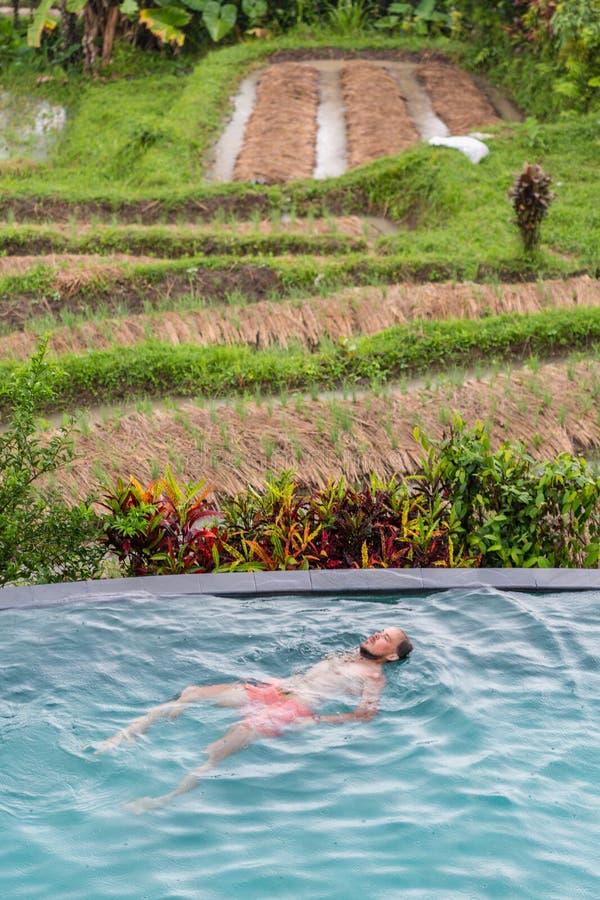Lyxig semesterort Man som kopplar av i oändlighetssimbassängvatten Härlig lycklig sund manlig modell Enjoying Summer Travel arkivbilder