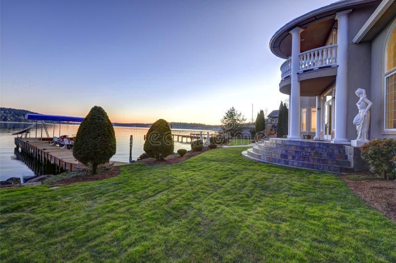 Lyxig sikt för strandhemträdgård på solnedgången royaltyfria bilder