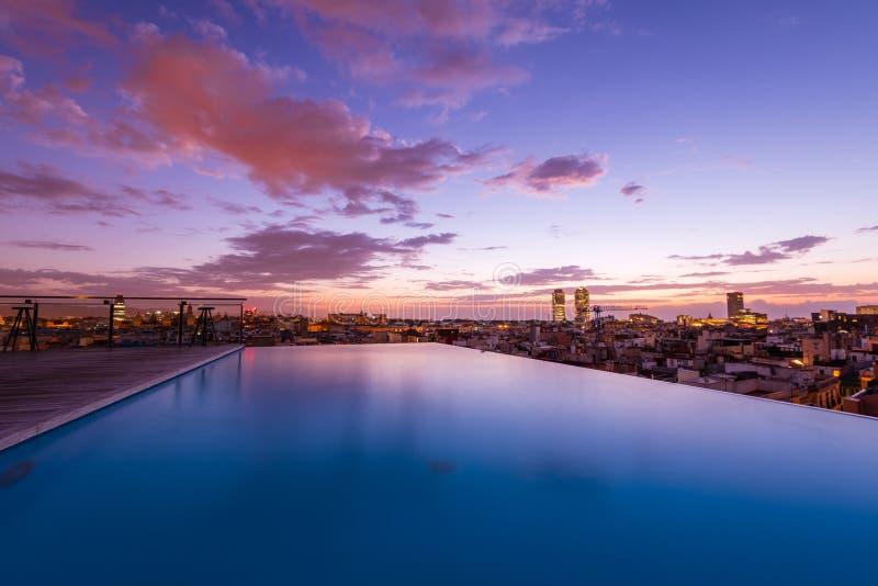 Lyxig taköverkantsimbassäng med en stadssikt arkivfoto