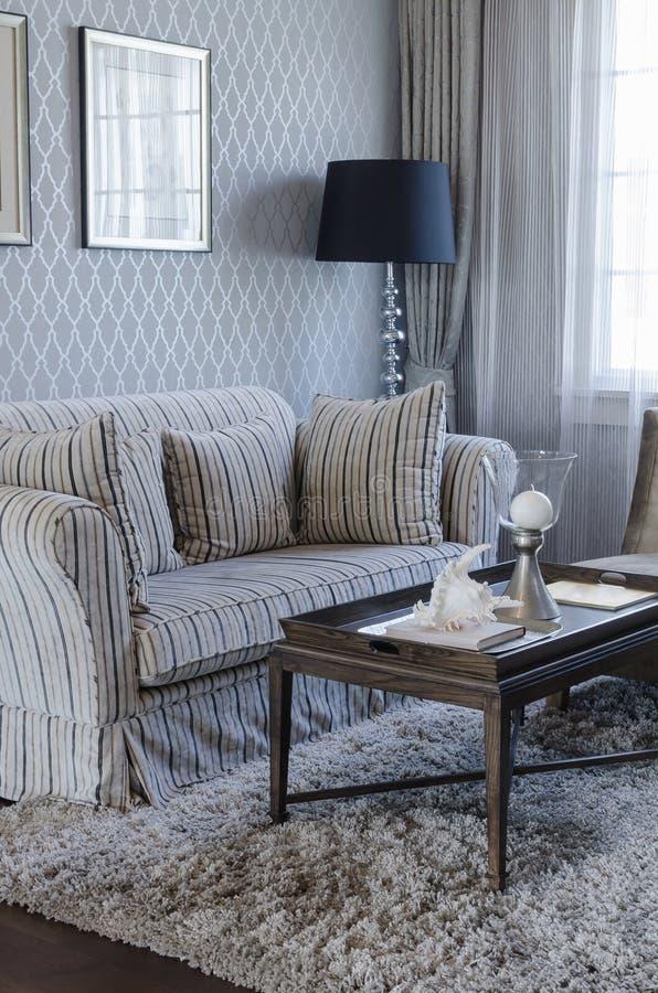 Lyxig vardagsrum med den klassiska soffan, kuddar och den svarta lampan arkivbilder